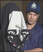 An Australian policeman leads a shrouded suspect away