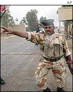 An Iraqi soldier clears journalists from a UN inspection of a plant in Samarah