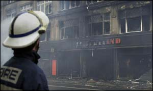 A firefighter observes the burnt-out shell of a building on Edinburghs South Bridge