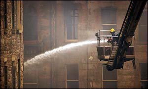 firefighter trains his hose on the burnt-out shell of a building in Edinburghs Cowgate