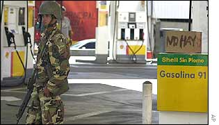 A solider guards an empty petrol station