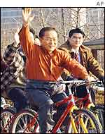 Lee Hoi-chang rides a bicycle with his supporters north of Seoul