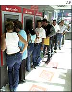 A line of people waiting to withdraw money