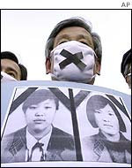 Protestor with photos of the dead girls