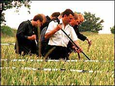 Photo of police searching fields near the Russell family home