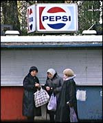 Women walking past Pepsi kiosk