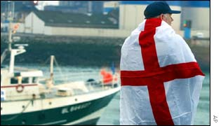 An unidentified fisherman stands on the port of Boulogne-sur-Mer, northern France, draped in the English flag