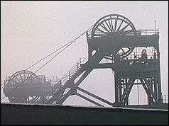 Coal mine pithead silhouetted against grey sky