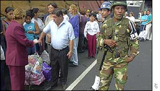 Venezuelans queue outside a supermarket