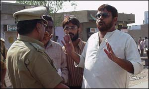 A voter argues with a police official at a polling station in Ahmedabad