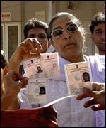 Angry voters in Juhapura wave their identity cards, alleging their names were missing from the voter list