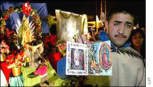 A man shows pictures of the Virgin of Guadalupe for sale