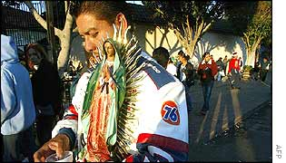 A man carries a statue of the Virgin of Guadalupe