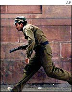 Policeman runs for cover outside Indian Parliament, 13 December, 2001