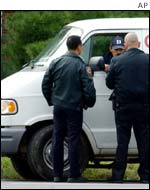 Law enforcement officers perform a spot check of a white van