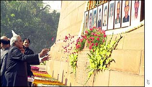 Prime Minister Atal Behari Vajpayee throws flower petals in front of the portraits of security personnel killed during the attack