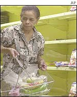 A customer selects an item from an almost bare shelves at a supermarket in Caracas