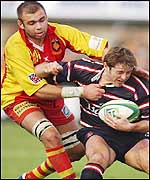 Gloucester scrum-half Andy Gomarsall is scragged by Gregory Le Corvec