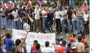 Chavez supporters (below) square off with opposition protesters in Caracas