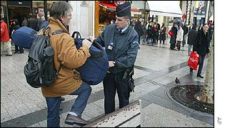 Police check a musician's bags on a Paris street