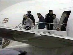Rowdy passengers being escorted from the plane, January 1999