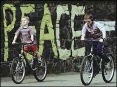 Children cycling by peace sign in Belfast