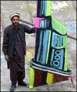 A painter holds a giant gun he produced