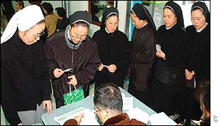 South Korean nuns have their IDs checked by Election Commission workers at a polling station in Busan