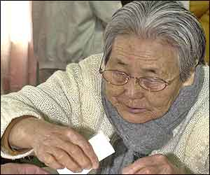 An elderly woman casts her ballot in presidential elections at a polling station in Jeju Island, South Korea
