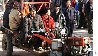 Farmers riding a tractor arrive as other voters stand in line to enter a polling station in Imsil County, South Korea