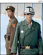 A North Korean soldier (left) looks at a South Korea soldier standing guard on the North-South border, August 2002
