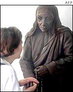 A Missionary of Charity volunteer in front of a statue of Mother Teresa in Calcutta