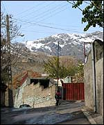 A street with the snow-capped Alborz Mountains in the background