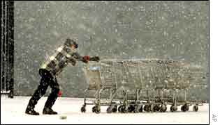 A Wal-Mart employee pushes shopping carts back toward a building in Missouri