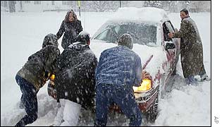 People push a car out of a driveway in Oneonta, New York