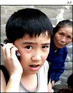 A young Chinese boy makes a call on a mobile phone during a visit to the Great Wall of China
