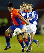 Michael Mols and Alan Mahood battle for possession