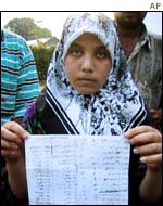 Zainab Ihsan, 12, survivor of the sinking refugee ship, holds a list of those missing.