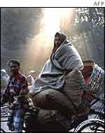 Man wrapped up travelling on a rickshaw in Dhaka