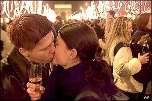 Two revellers kiss on the Champs Elysees in Paris