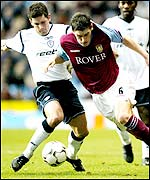 Gareth Barry drives forward for Aston Villa as Anthony Barness tries to get his challenge in