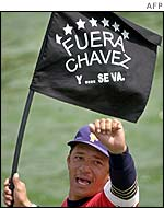 A protestor waves a flag with an anti-Chavez slogan