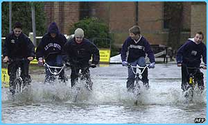 Kids in near Reading ride their bikes through the water