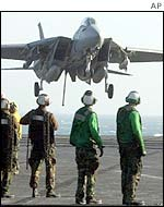 A fighter jet comes in to land, watched by crew on the USS Constellation