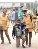 Police tackle a protester in Patna