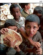 Boys receive food handouts in Karachi