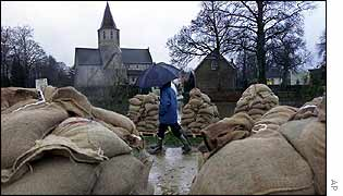 Walkers pass a pile of sandbags at the village of Afsnee