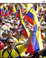 Opposition supporters wave flags as they parade down to Fuerte Tiuna in Caracas