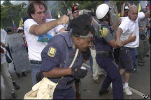 An opposition protester, left, hits a police officer who was firing tear gas, during clashes near Fuerte Tiuna military base in Caracas