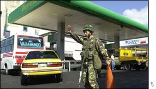 A Venezuelan army soldier directs traffic at the entrance to a gas station in Caracas